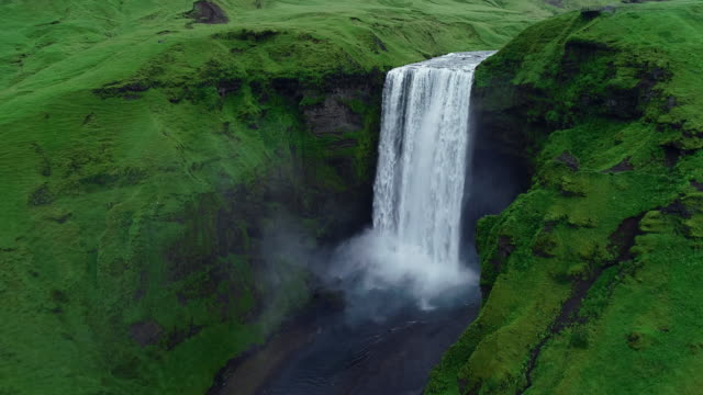 slow motion aerial view of magnificent famous waterfall skogafoss in iceland - landmarks stock videos and b-roll footage