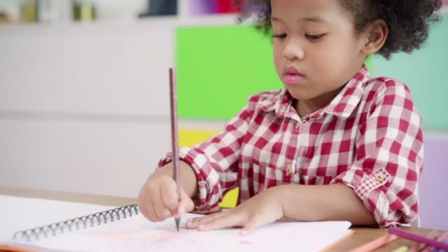 slow motion - bambini africani che disegnano e fanno i compiti in classe, giovane ragazza felice studio divertente e giocare a dipingere su carta alle elementari. disegno e pittura per bambini a scuola concept. - matita colorata video stock e b–roll