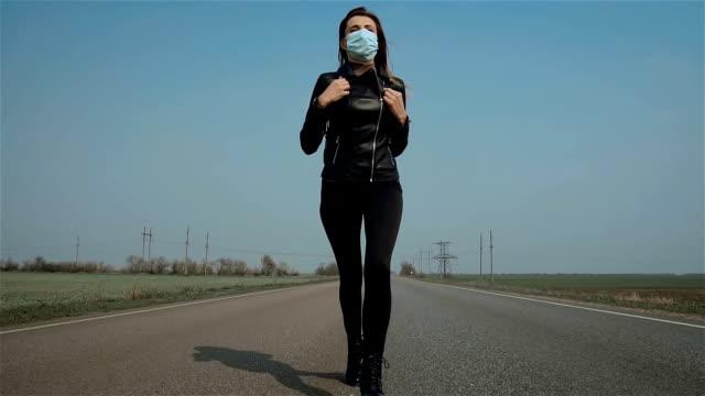 Slow motion ensam kvinna i ansiktet skyddande mask springer bort från infektion på väg långt från människor och stad för att rädda livet video