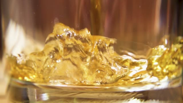Slow motion amber drink pour into a glass close-up