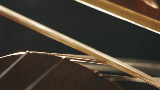 Slow motion artistic macro of master artisan luthier playing with a bow on a handmade violin or cello