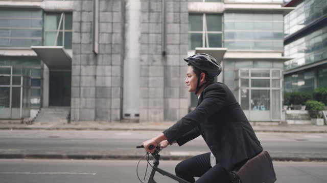 Slow motion Asian businessman in a suit is riding a bicycle on the city streets for his morning commute to work. Eco Transportation Concept.