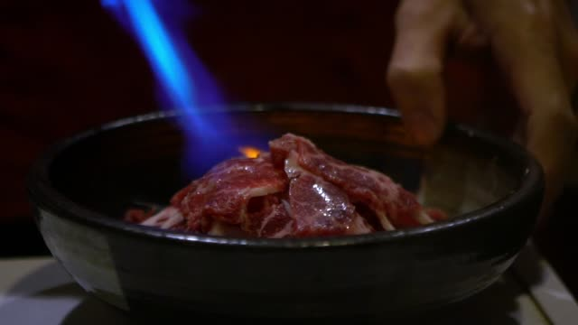 vídeos de stock e filmes b-roll de slow motion asian cheff burns slice of raw beef with blowtorch in restaurant - burned cooking