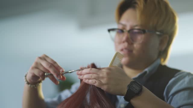 slow motion Asian chinese hairstylist female cutting hair for her customer in hair saloon
