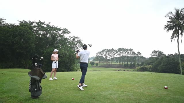 slow motion Asian chinese male golfer teeing off at golf course with his wife beside