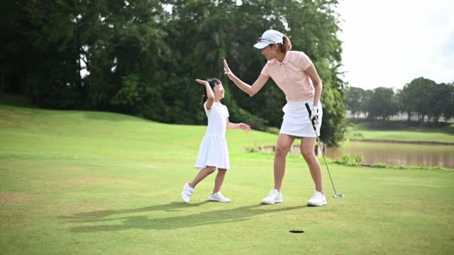 slow motion Asian chinese parent golfer teaching daughter playing golf at golf course weekend