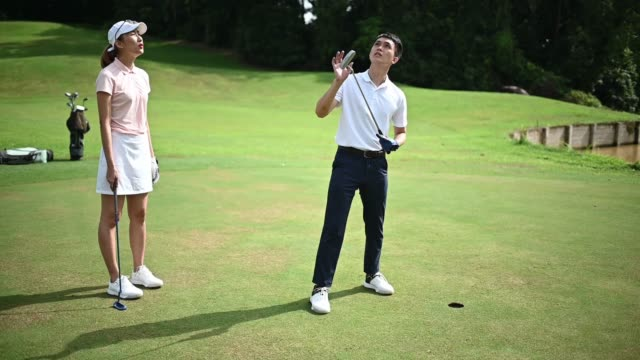 slow motion Asian chinese young couple golfer at putting green