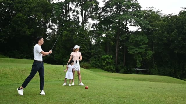 slow motion Asian chinese young couple golfer teeing off and swing his driver club on the golf course