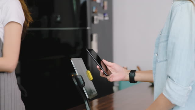 slow motion asian customer order coffee from tablet and use mobile phone pay contactless with tablet at counter bar in cafe.small business start up.customer service concept - digital mobile consumption video stock e b–roll