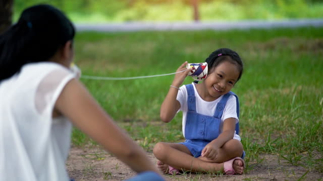 Slow motion, Asian family, mother and daughter doing string phone play activities tie rope at the park.