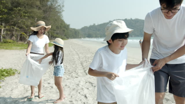 4K UHD Slow motion : Asian family picking up plastic bottle to trash bag on the outdoor beach. Father teaching son for awareness environment and save the world by recycle plastic bottle. 4K UHD Slow motion : Asian family picking up plastic bottle to trash bag on the outdoor beach. Father teaching son for awareness environment and save the world by recycle plastic bottle. environmental consciousness stock videos & royalty-free footage
