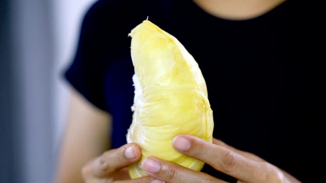 Slow motion Asian woman eating fresh peel Durian.