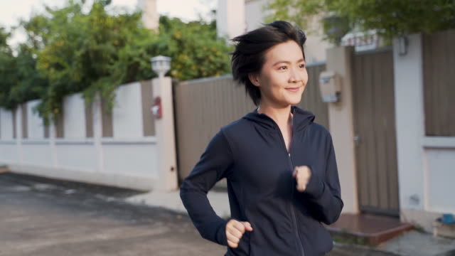Slow motion: Asian woman running on road, Len flare Steadicam shot