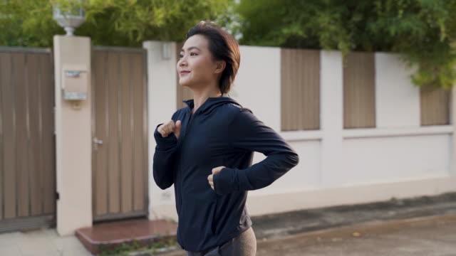 Slow motion: Asian woman running on road, Len flare Steadicam shot