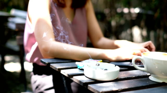 4K Slow motion : Asian Woman taking break from her work to smoking cigarette in coffee cafe.