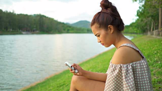 Slow motion Asian women using smartphone near river video