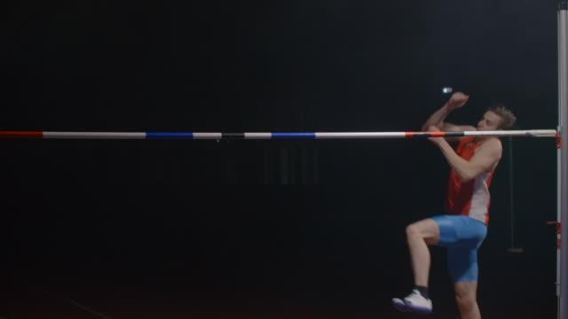 vidéos et rushes de ralenti: athlète faisant le succès de saut en hauteur - homme slip