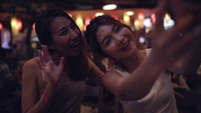 Slow motion - Backpacker Asian women lesbian lgbt couple taking selfie drinking alcohol or beer with friend and party at Khao San Road in Bangkok, Thailand. Lifestyle women party with friends concept. video
