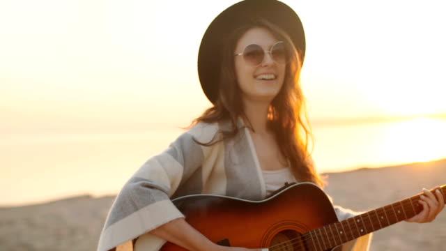 замедленная съемка. красивая девушка играет на гитаре на пшеничное поле - аксессуар для волос стоковые видео и кадры b-roll