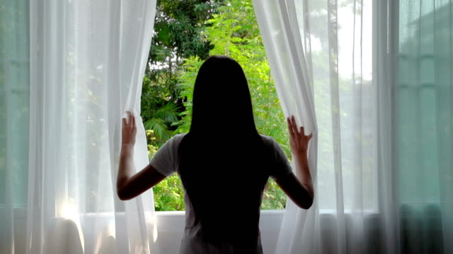 vídeos de stock, filmes e b-roll de câmara lenta, cabelo longo bonito das mulheres asiáticas do cabelo longo que abrem a cortina na manhã - janela