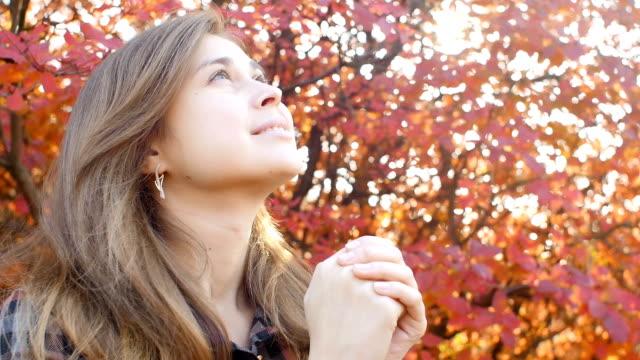 vidéos et rushes de belle femme de mouvement lent appréciant jouant le violon sur un fond des feuilles rouges d'automne, visage de fille romantique engagée dans l'art musical, exécution sur la nature, concept du passe-temps - vue en contre plongée verticale
