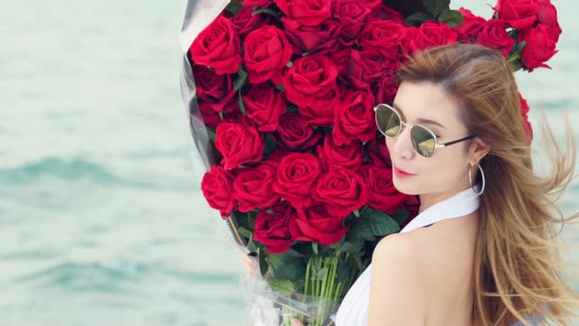 Slow motion beautiful woman red roses valentine bouquet romantic gift sea vacation trip.