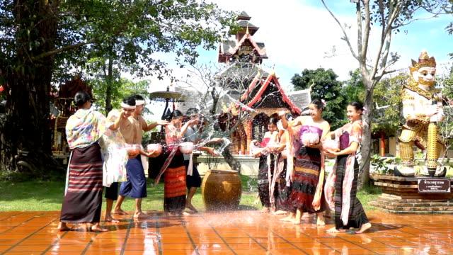 vídeos de stock, filmes e b-roll de slow motion: mulheres bonitas desgaste traditionnel traje tailandês espirrando água em homens no templo-songkran festival - ano novo budista