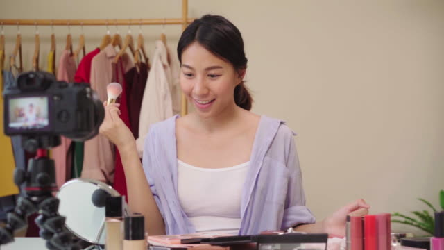 Slow motion - Beauty blogger present beauty cosmetics sitting in front camera for recording video. Happy beautiful young Asian woman use cosmetics review make up tutorial broadcast live video.