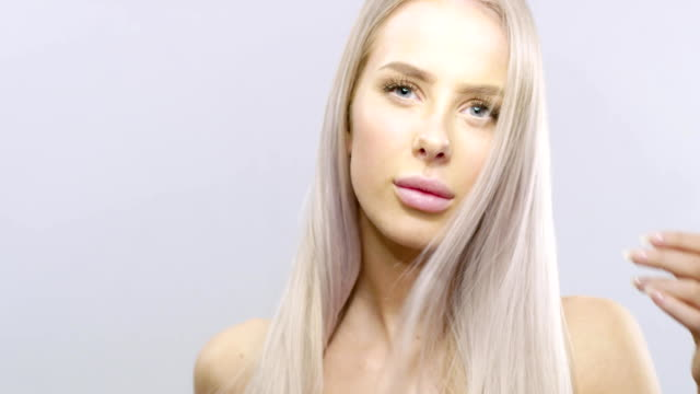 Slow motion beauty portrait of a blonde woman's hair blowing in the wind video