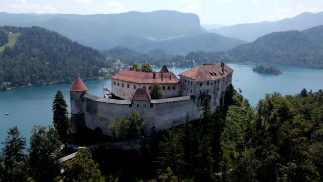 AERIAL, slow motion: Bled Castle with lake island in the background video