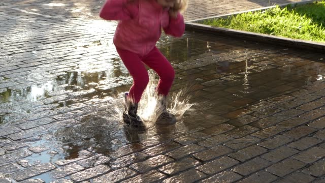 Slow motion blonde child in pink jumps on puddles, splashes scatter from boots. video
