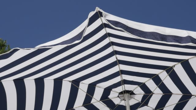 slow motion blue beach parasol and clear sky - penombra video stock e b–roll