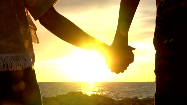 Slow motion blurred point of view medium shot rear view silhouette young adult couple man and woman tourist holding hand together walking forward to rocky sea coast at summer sunset with twilight sky on holiday vacations with lens flare. Rear view SLO MO  POV MS man and woman holding hand together walking forward to rocky sea coast back lit stock videos & royalty-free footage