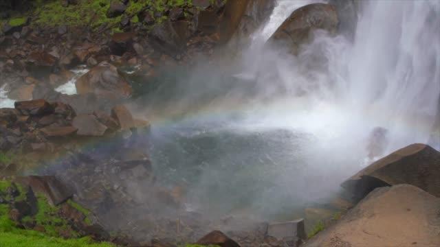 zeitlupe nab des rauschenden wasserfalls, der felsen trifft und einen regenbogen erzeugt - kaskaden gebirge stock-videos und b-roll-filmmaterial
