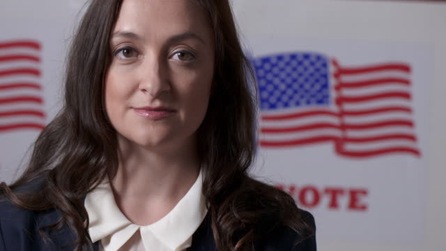 Slow motion business woman stands in front of voting booths 4K video