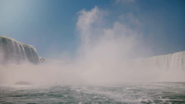 Slow motion camera approaches large cloud of white water spray mist rising over epic Niagara Falls waterfall scenery.