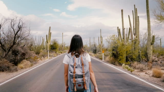 Slow motion camera follows young happy tourist woman with backpack walking on hot desert road in Saguaro cactus park.