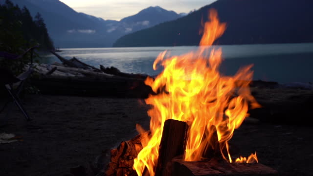 slow motion campfire on sand in front of a beautiful lake slow motion campfire on sand in front of a beautiful glacier lake at early morning bonfire stock videos & royalty-free footage