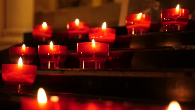 Slow motion Catholic prayer red cup votive candles in candle rack