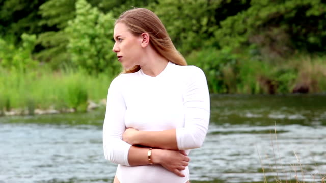 Slow Motion Caucasian Woman Blond Half-Length Standing With River In Background Blond Caucasian Woman Half-Length In White Leotard Standing With River In Background Slow Motion leotard stock videos & royalty-free footage