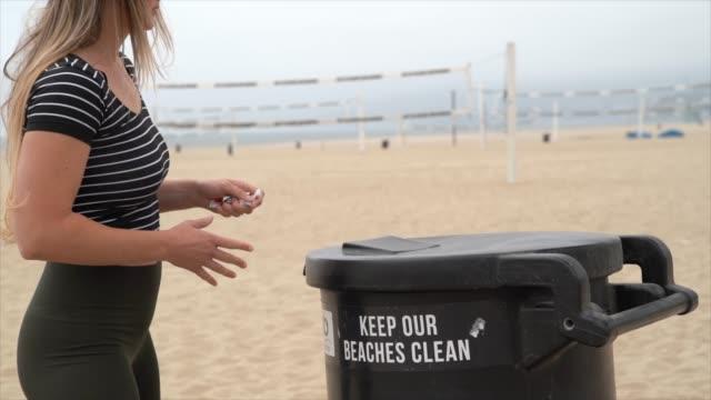 ralenti femme caucasienne jette loin Trash à la plage - Vidéo