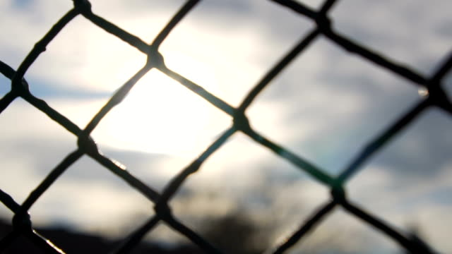 vídeos de stock e filmes b-roll de slow motion: chain fence against golden sun - cercado