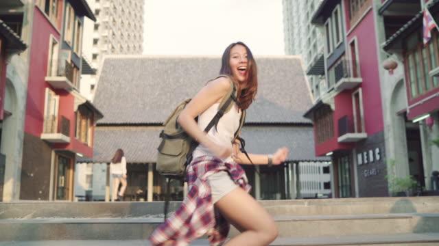 vídeos de stock, filmes e b-roll de câmera lenta - alegre linda jovem mochileiro asiáticos blogger mulher sentindo feliz dançando na rua enquanto viajava em chinatown em pequim, china. conceito de férias viagens turísticas de mochila de estilo de vida. - moda street