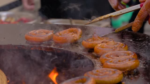 Slow motion: chef grilling fresh spiral pork sausages on brazier with hot flame
