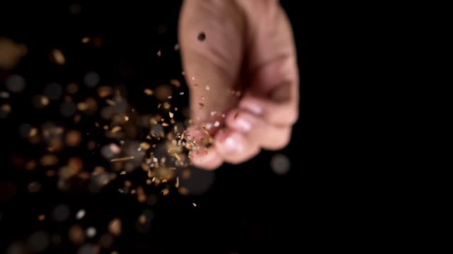 Slow motion: Chef hand in and sprinkling seasoning on top of camera. Slow motion with center composition: Chef hand in and sprinkling seasoning on top of camera. Copy space and black background. spice stock videos & royalty-free footage