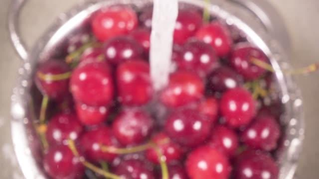Slow motion cherry in colander under water video