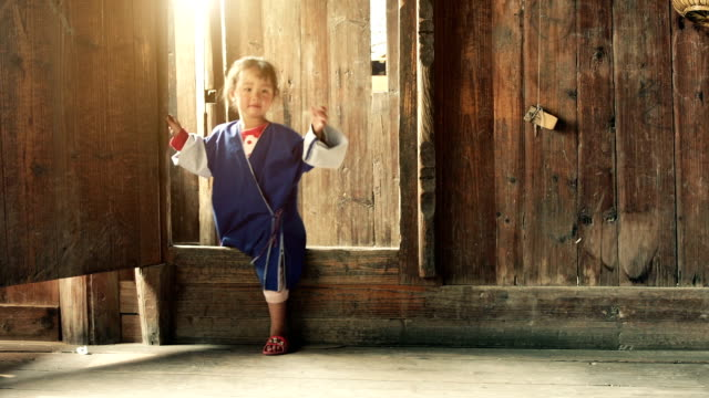 slow motion: chinese female child walking into a wooden house - burma home do stok videoları ve detay görüntü çekimi