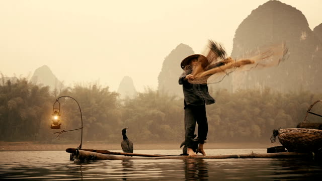Slow motion Chinese fisherman throwing net on river Lee