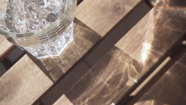 Slow motion clean water flows into the glass on the table