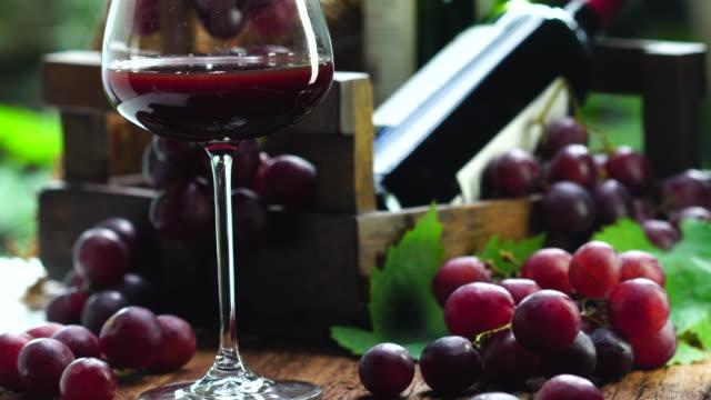 クリスタルグラスに赤ワインをドロップのスローモーションクリップ、有機新鮮なブドウと背景に空のボトル、ドリンクのアイデアの概念、テキストのための空きスペースの最高。 - 赤ワイン点の映像素材/bロール